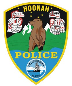 The patch of the Hoonah, Alaska, Police Department honors many natural wonders of the city and surrounding areas. Hoonah and nearby Chicagof Island have the highest per-capita grizzly bear population of any city in the world, hence the one in the center. Eagle and raven totem poles honor the Tlingit and Haida Indian Tribes. The snow-capped mountains capture the scenic landscape of Chicagof Island, and the water beneath them depicts the inland passage to the Pacific Ocean. The fishing boat at the bottom recognizes the importance of the local fishing industry.