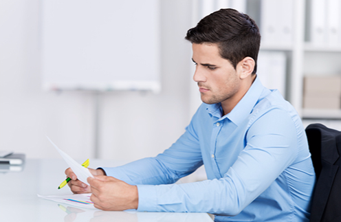 Stock image of a man reading a document in a workplace setting with a highlighter in his hand.