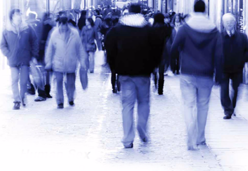 Blurred image of people walking on a sidewalk. Stock image.