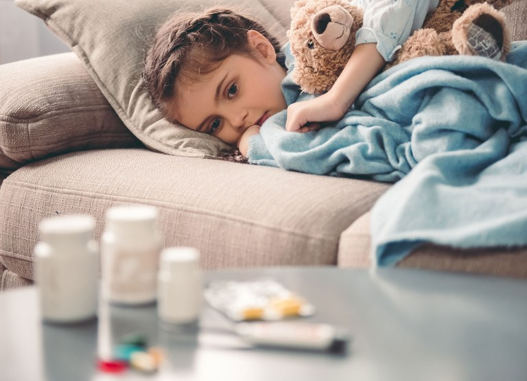 A stock image of a young female child laying on the couch with medications on the table in front of her.