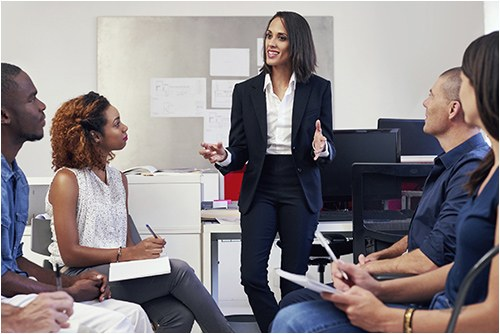 Stock image of a woman talking to colleagues at work.