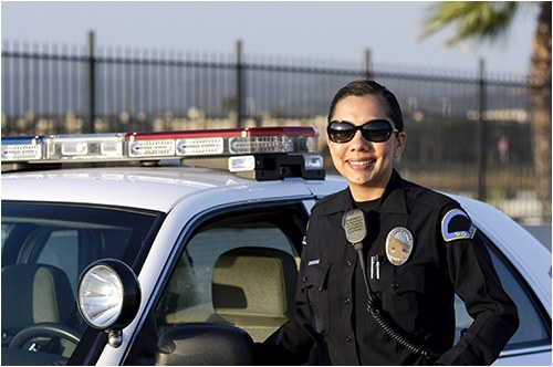 A female police officer in uniform stands next to a police vehicle.