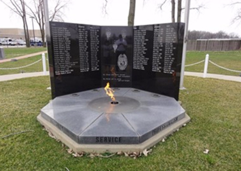 The Indiana State Police Memorial, located on the east side of Indianapolis, consists of three black granite tablets and an eternal flame.