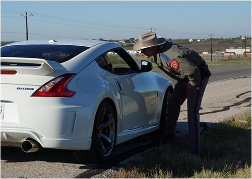 Stock image of an officer with the Texas Department of Public Safety talks to the driver of a white car who has been pulled over.