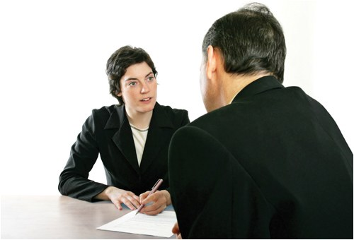 Stock image of a woman interviewing a man, with both sitting around a table.