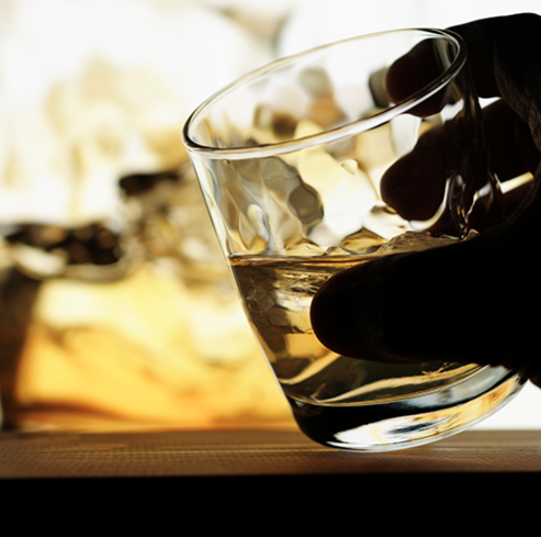 Stock image of hard liquor in a glass being held by an individual.