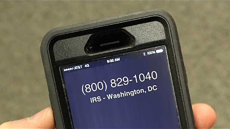 An image of a cell phone screen with an IRS scam number appearing as an incoming call.