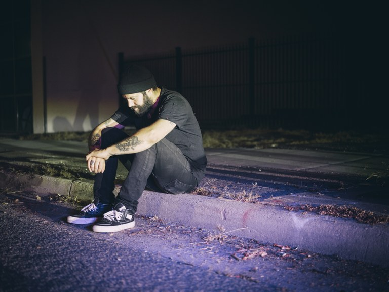 A stock image of a man sitting on a curb.