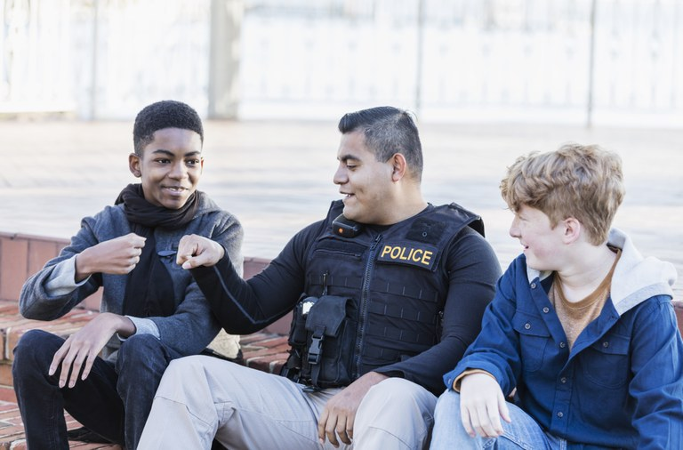 A stock image of a male officer talking to two teenage boys.