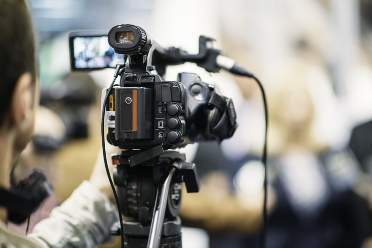 A stock image of a cameraman recording video footage.