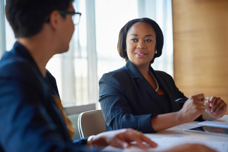 A stock image of two females business women speaking.