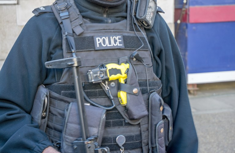 A stock image of a police officer with a taser gun attached to his vest.