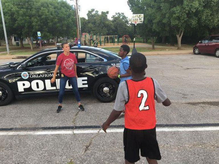 A female officer playing basketball with two boys.