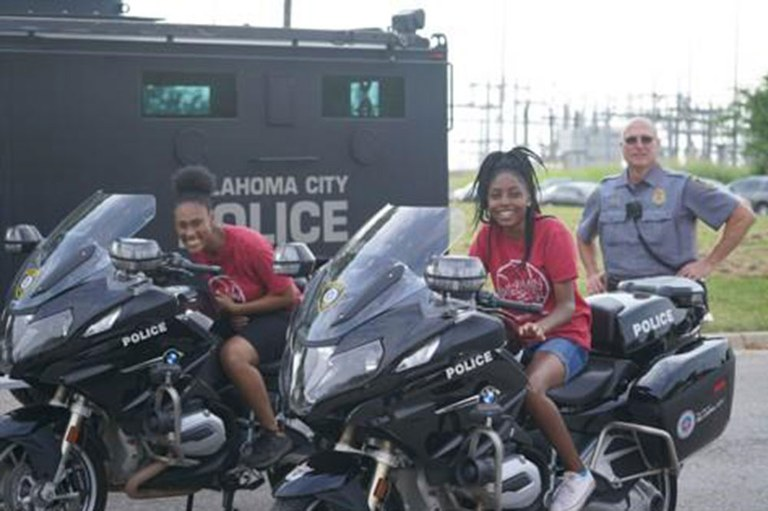 Two teenage girls sitting on Oklahoma City police motorcycles with an officer in the background.