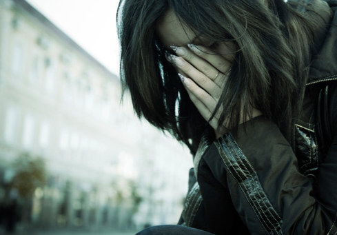 Stock image of a woman crying outside a building.