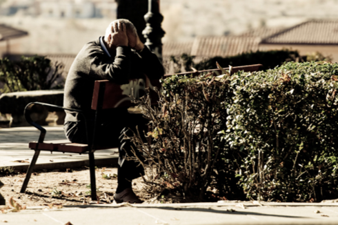 Stock image of a man on a park bench with his head in his hands.