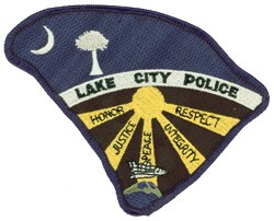 "The patch of the Lake City, South Carolina, Police Department is in the shape of the state and displays the half-moon and palmetto tree, like South Carolina's flag. The Challenger space shuttle honors Ron McNair, an astronaut from Lake City. Rays of the sun feature the words ""honor,"" ""justice,"" ""peace,"" ""integrity,"" and ""respect,"" character traits of a police officer."