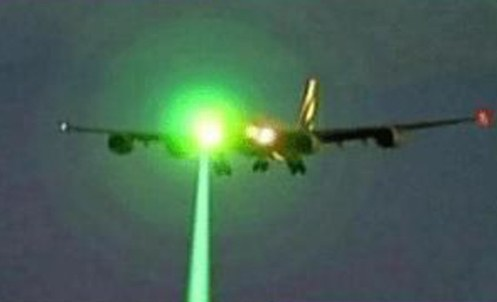 A laser strike is shown hitting the outside of a commercial airliner.