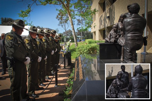 "The San Diego County Law Enforcement Memorial was dedicated on May 10, 2011. The bronze statue, entitled ""A Tribute to Service, the Ultimate Sacrifice,"" depicts a kneeling sheriff presenting a folded American flag to a grieving widow and her son."