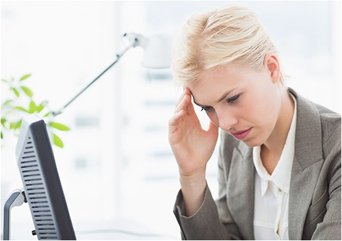 Stock image of a woman sitting in front of a computer monitor with her hand to her head.