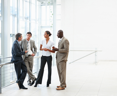 Stock image of a group of employees have a discussion in an atrium-type atmosphere.