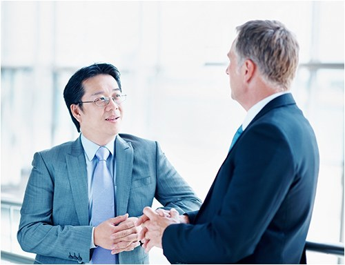 Stock image of two men talking at work.