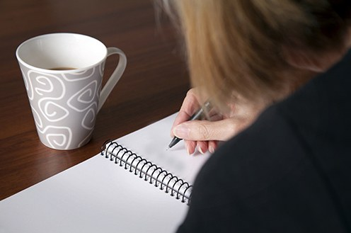 Stock image of a woman writing in a blank notebook with a coffee cup above it.