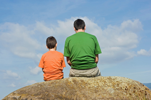 Stock image of a father and son sitting on a boulder outside.