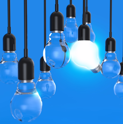 Stock image of multiple hanging light bulbs, including one that is lit.