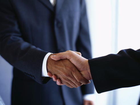 Stock image of two men shaking hands in an office.