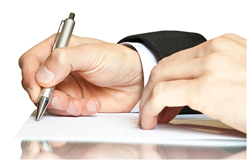 Man Writing a Note with a Pen (Stock Image)