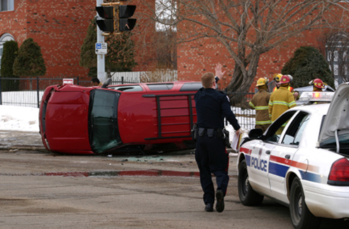 First responders and a police officer at the scene of an automobile accident.