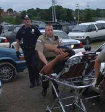 An officer moves an injured victim from the scene of an incident.