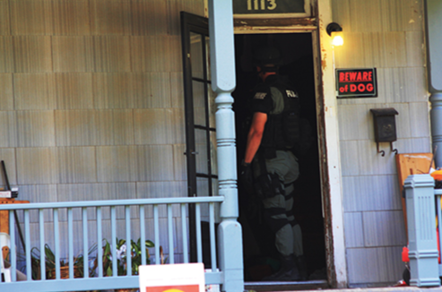 A law enforcement officer executes a search warrant on a suspect's house.
