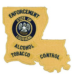 The Louisiana Office of Alcohol and Tobacco Control patch is in the state's distinct boot-like shape. At the center, the Louisiana seal shows a pelican, the state bird, with its head turned to the left in a nest while feeding its three young.