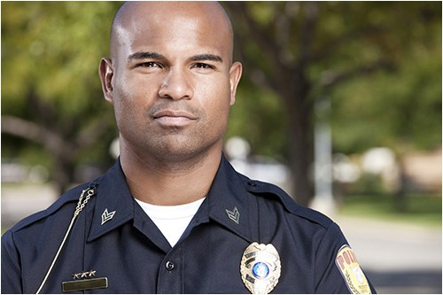 Stock image of a male police officer in uniform outside.