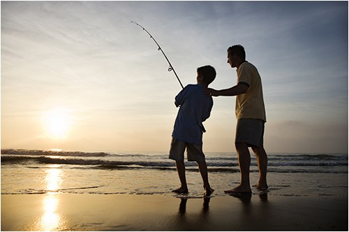Stock image of a man and his son fishing in the ocean.