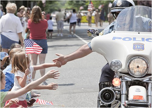 A police officer on a motorcycle low-fives young kids holding American flags.