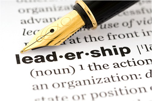 "A stock image of a fountain pen pointing to the word ""leadership"" in a dictionary."