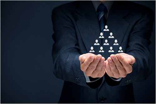 Stock image of man holding a triangle of human figures.