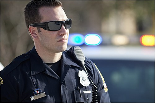 A police officer outside wearing sunglasses with a vehicle in the background.