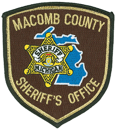 Macomb County, Michigan, was formally organized on January 15, 1818, and named after Major General Alexander Macomb, Jr., a highly decorated veteran of the War of 1812. The county encompasses 482 square miles and, with over 850,000 residents, ranks third in population in the state. The city of Detroit is located below the county's southern border, along 8 Mile Road. The patch of the Macomb County Sheriff's Office features an outline of the state in blue behind a six-point sheriff's star. At the center of the gold badge is the Michigan state seal.