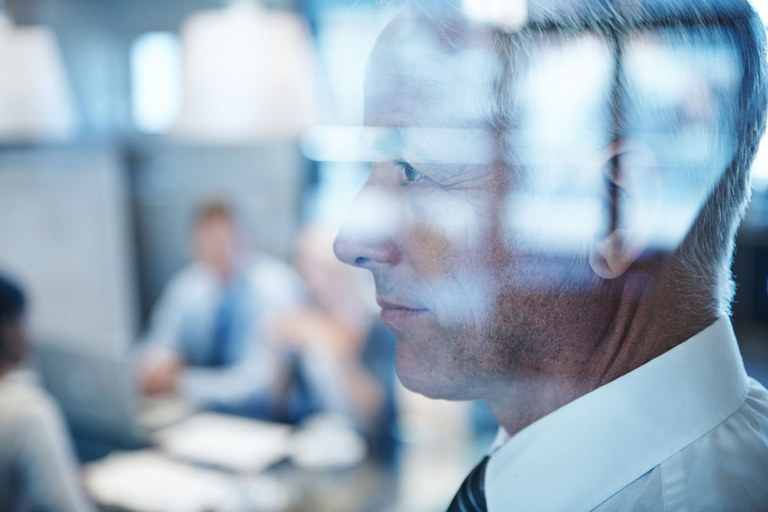 Stock photo of a male business man looking out a window in a conference room.