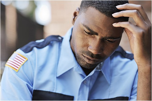 A distressed or worried male police officer with his hand on his head.