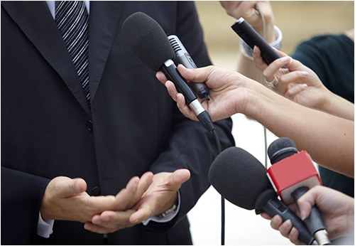 Stock image of a man speaking to the media.