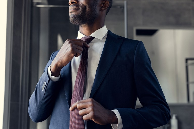 A stock image of a man in business attire adjusting his tie.