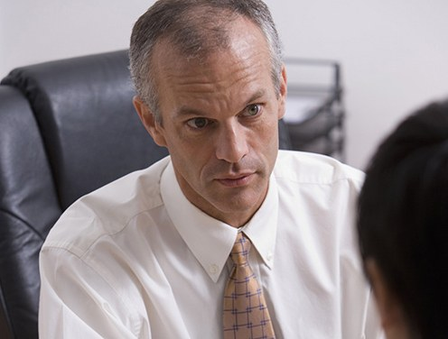 Stock image of a man interviewing a person in an office.