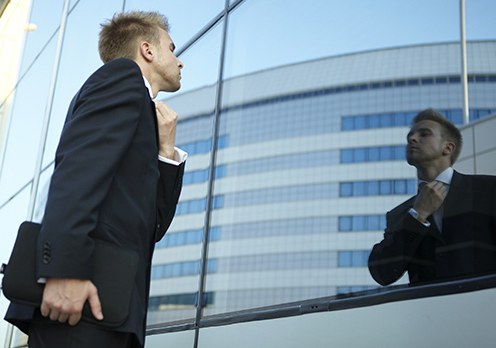 Stock image of a businessman fixing his tie using a glass building as a mirror.