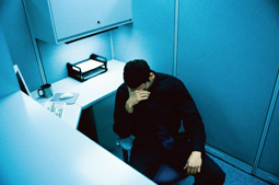 A man sitting in a chair in his work cubicle with his head in his hand. © Thinkstock.com.