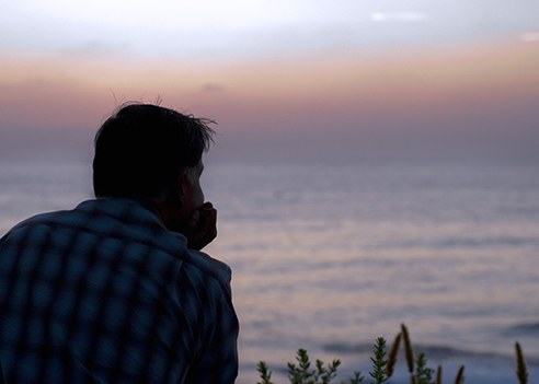 Stock image of a man looking at the ocean during a sunset.